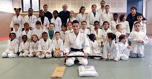 Rayan dans le dojo du gymnase Paul-Langevin pose devant la relève du club  avec sa ceinture noire gravée à son nom, son sabre katana et son kimono de  ... 2e8721cf0dd